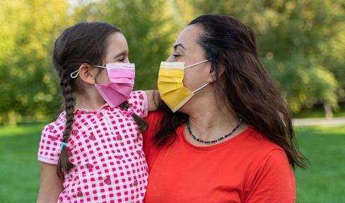 Mutter und Tochter lachend mit Maske auf Wiese